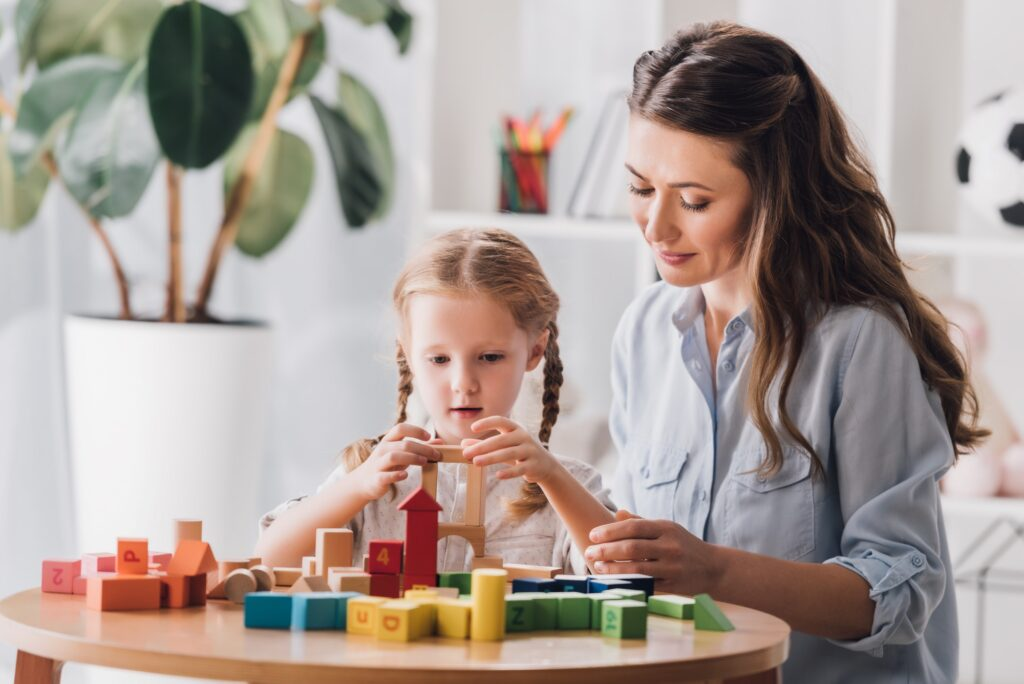 psychologist playing blocks with little child with autism syndrome